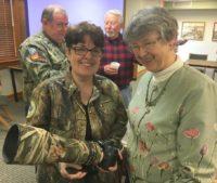 Teresa McGill shows Diane Strzelinski one of the telephoto lenses she uses when photographing wildlife.